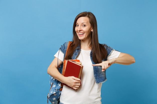 Portret van jonge opgewonden lachende vrouw student met rugzak met schoolboeken wijzende wijsvinger op kopie ruimte geïsoleerd op blauwe achtergrond. onderwijs in het concept van de middelbare schooluniversiteit.