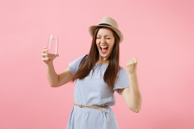 Portret van jonge opgewonden vrouw in blauwe jurk, hoed vasthouden en drinken van helder vers zuiver water uit glas geïsoleerd op roze achtergrond. gezonde levensstijl, mensen, oprechte emoties concept. ruimte kopiëren.