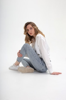 Portret van jonge peinzende blanke vrouw poseren in shirt en spijkerbroek, zittend op een witte vloer. modelproeven van mooi meisje in basiskleren op cyclorama