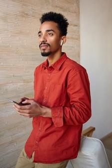 Portret van jonge peinzende kortharige krullende brunette man met donkere huid bedachtzaam vooruit kijken terwijl het houden van mobiele telefoon in opgeheven handen, poseren op beige interieur