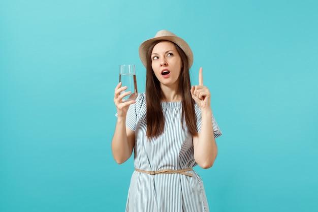 Portret van jonge peinzende vrouw in blauwe jurk, hoed vasthouden en drinken van helder vers zuiver water uit glas geïsoleerd op blauwe achtergrond. gezonde levensstijl, mensen oprechte emoties concept. ruimte kopiëren.