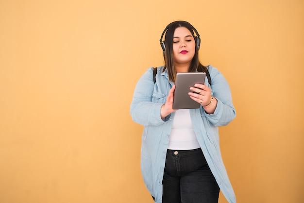 Portret van jonge plus grootte vrouw die aan muziek met hoofdtelefoons en digitale tablet in openlucht tegen geel luistert