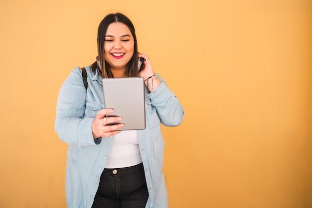 Portret van jonge plus grootte vrouw die aan muziek met hoofdtelefoons en digitale tablet in openlucht tegen gele achtergrond luistert.