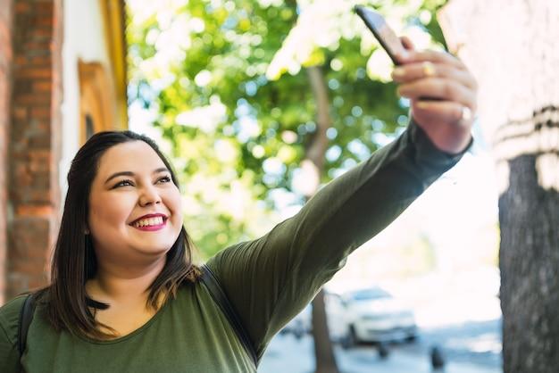 Portret van jonge plus grootte vrouw die selfies met haar mophile telefoon buiten op straat neemt. stedelijk concept.