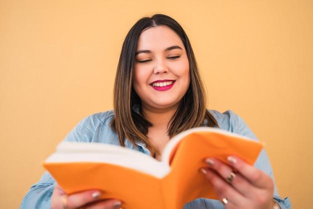 Portret van jonge plus groottevrouw die van vrije tijd geniet en een boek leest