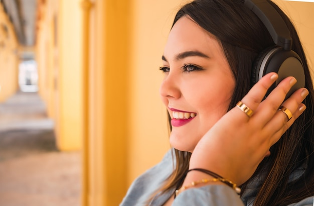 Portret van jonge plus size vrouw die buiten naar muziek luistert met een koptelefoon headphones