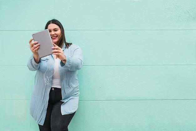 Portret van jonge plus size vrouw, luisteren naar muziek met oortelefoons en digitale tablet buitenshuis.