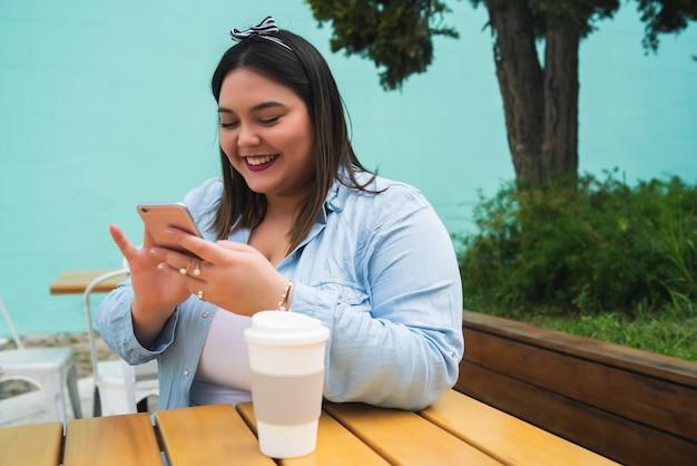 Portret van jonge plus size vrouw met behulp van haar mobiele telefoon tijdens de vergadering in coffeeshop. communicatie- en technologieconcept.