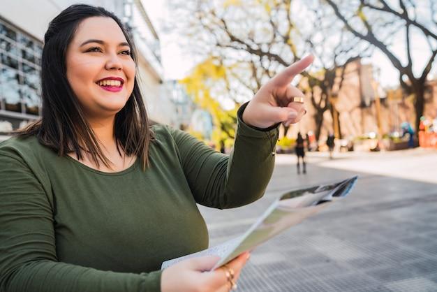 Portret van jonge plus size vrouw met een kaart en op zoek naar een routebeschrijving buiten in de straat. reis concept.
