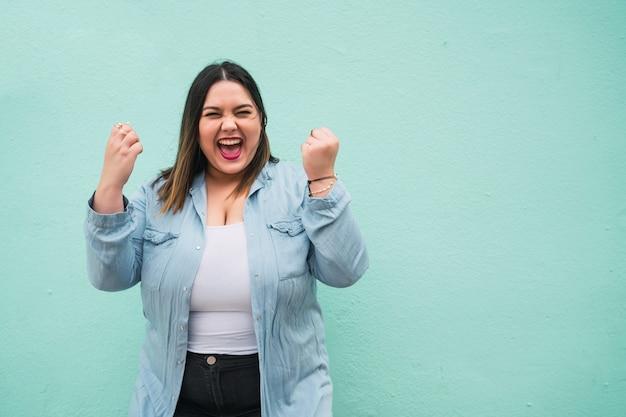 Portret van jonge plus size vrouw vieren overwinning buiten op lichtblauw. succes concept.