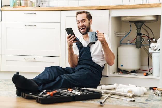 Portret van jonge positief lachende man loodgieter werk in uniform binnenshuis met behulp van mobiele telefoon koffie drinken.