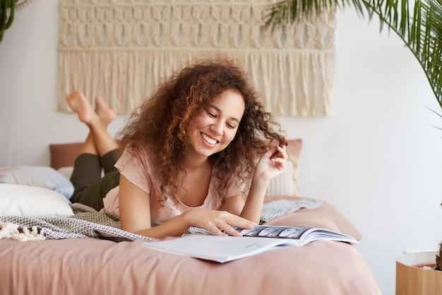 Portret van jonge positieve afro-amerikaanse dame met krullend haar, ligt op het bed en geniet van vrije dag, breed lacht en ziet er gelukkig uit, leest een nieuw nummer van het tijdschrift.
