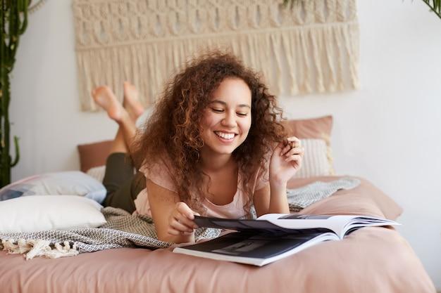 Portret van jonge positieve afro-amerikaanse dame met krullend haar, ligt op het bed en leest een nieuw nummer van het tijdschrift, geniet van vrije dag, glimlacht breed en ziet er gelukkig uit.