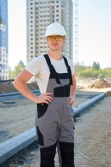 Portret van jonge positieve bouwer die witte beschermende helm en werkende overall draagt