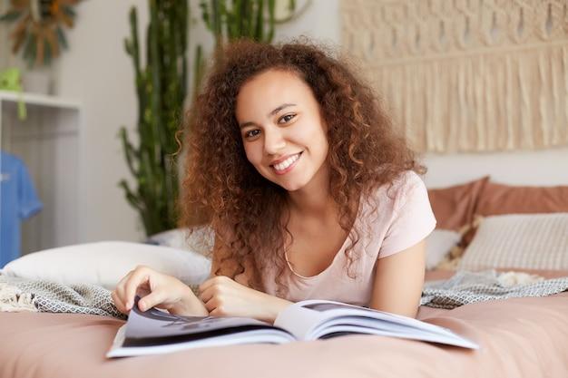 Portret van jonge positieve donkere vrouw met krullend haar, ligt op het bed en leest een nieuwe uitgave van favoriete tijdschrift, geniet van zonnige vrije dag, kijkt naar de camera en glimlacht breed.