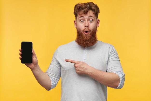 Portret van jonge positieve roodharige man met grote baard, wijzend met een vinger naar het display van zijn telefoon met lege zwarte kopie ruimte