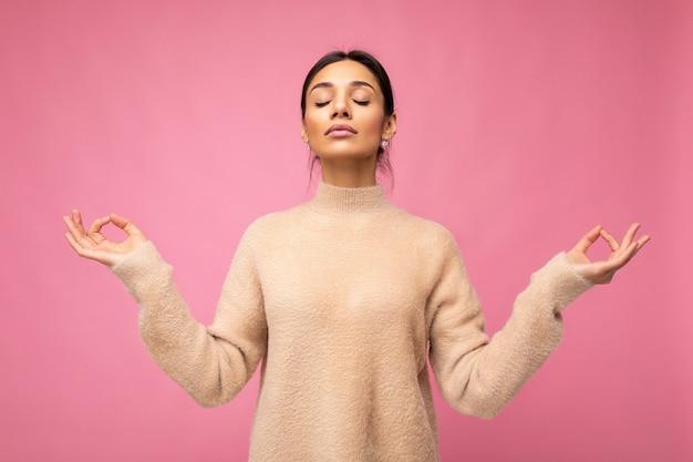 Portret van jonge positieve rustige gelukkig aantrekkelijke brunette vrouw met oprechte emoties dragen beige trui geïsoleerd over roze achtergrond met kopie ruimte en bemiddeling doen. yoga-concept.