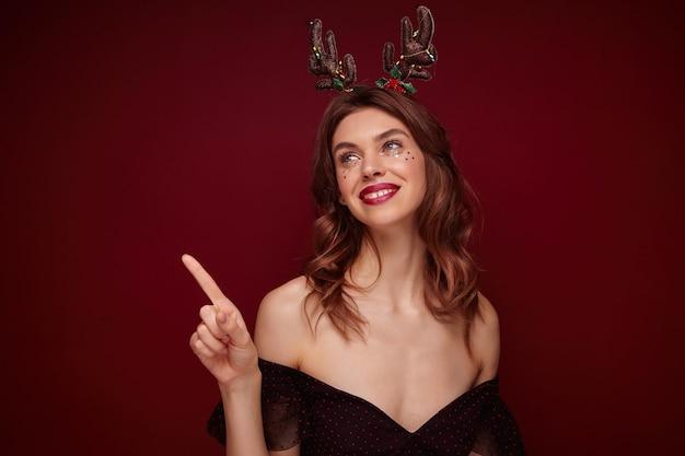 Portret van jonge positieve vrij bruinharige vrouw met golvend kapsel gelukkig opzij kijken en oprecht glimlachen, nieuwjaarsfeest voorbereiden en vakantie hoorns dragen