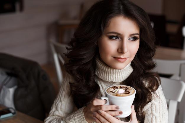 Portret van jonge prachtige vrouw die thee drinkt en bedachtzaam uit het raam van het café kijkt, genietend van haar vrije tijd, mooie zakelijke vrouwen lunch in het café in hun vrije tijd