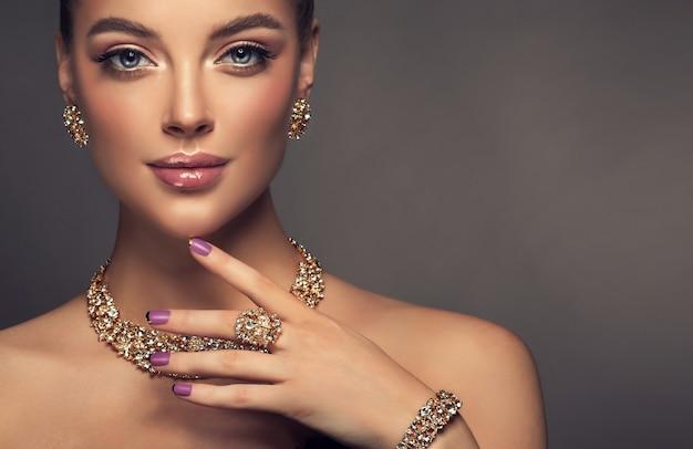 Portret van jonge prachtige vrouw gekleed in een prachtige make-up met lange zwarte wimpers en donkere roze lippenstift mooi model wordt aangebracht in modieuze sieraden set