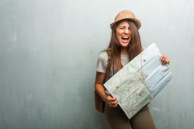 Portret van jonge reiziger latijnse vrouw tegen een muur boos gillen