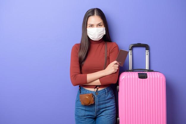 Portret van jonge reizigersvrouw met gezichtsmasker, nieuw normaal reisconcept