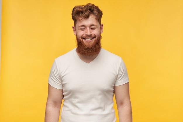 Portret van jonge roodharige bebaarde man draagt wit t-shirt houdt zijn ogen gesloten en glimlachen. voelt zich gelukkig op geel