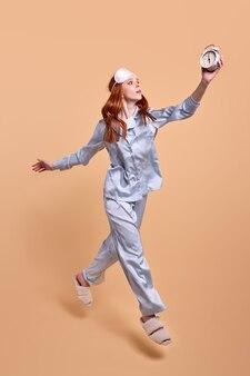 Portret van jonge roodharige vrouw springen, klokken in handen dragen, geïsoleerd op beige achtergrond in studio, opzoeken, in blauwe pyjama en oogmasker. slaap, ochtendconcept