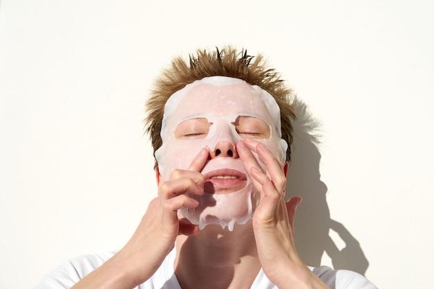 Portret van jonge roodharigevrouw die met leuk kapsel weefsel gezichtsmasker op gezicht toepassen