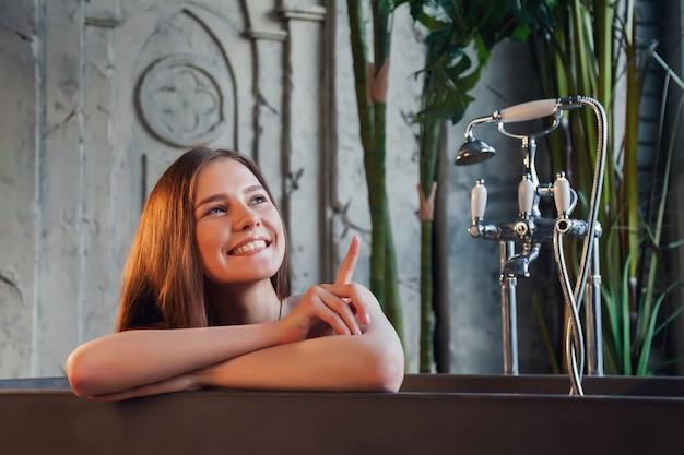Portret van jonge schattige vrolijke vrouw in badkuip toont vingers en kijkt weg over oude interieur badkamer. reclameconcept van gezonde levensstijl en zelfzorg. ruimte kopiëren voor site of spa