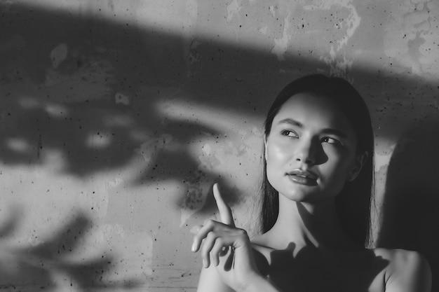 Portret van jonge schattige vrolijke vrouw toont vinger en kijkt weg over oude muurachtergrond met schaduw van blad. reclameconcept van gezonde levensstijl en zelfzorg. ruimte kopiëren voor site of spa