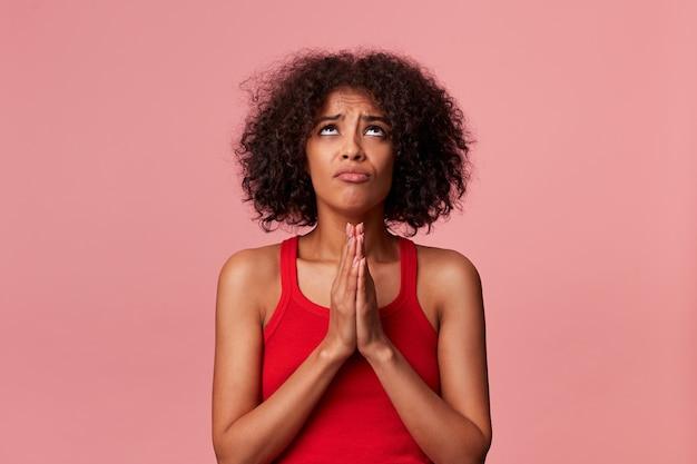Portret van jonge schoonheid african american meisje met donker krullend haar, gekleed in een rood t-shirt. loop op, houdt de handpalmen bij elkaar, verheugd over genade. geïsoleerd.