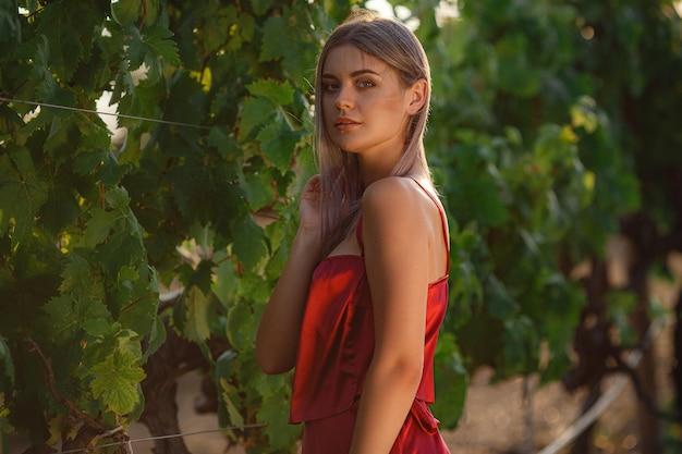 Portret van jonge schoonheidsdame in rode jurk in de wijngaarden in het zomerseizoen. genieten van een degustatietour in een prachtige wijnmakerij.