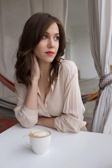 Portret van jonge sensuele vrouw het drinken koffie op een koffieveranda. concept van ontspanning en vrije tijd in de stad