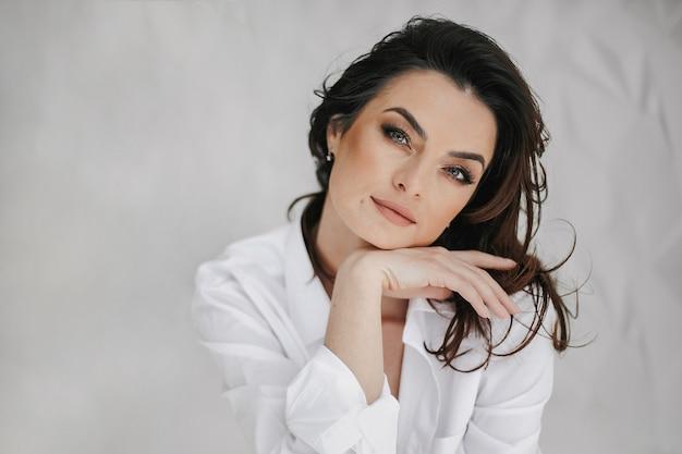 Portret van jonge sexy vrouw met make-up op witte achtergrond met blik, duidelijk gezicht aan te raken en er recht uit te zien.