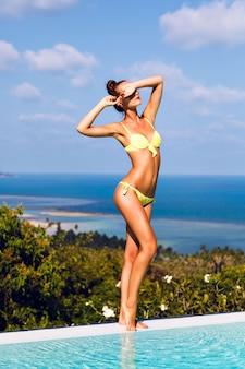 Portret van jonge sexy vrouw met perfect gebruinde slanke lichaam, het dragen van bikini en zonnebril, genieten van op vakantie. prachtig uitzicht vanaf de dwaas op het eiland