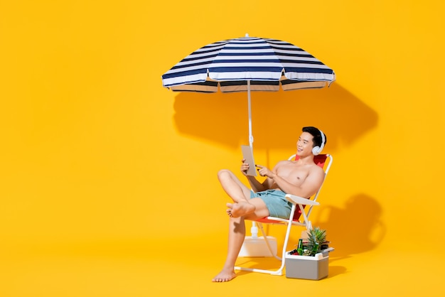 Portret van jonge shirtless aziatische mensenzitting op strandstoel die en aan muziek in geïsoleerde de zomer gele muur ontspannen luisteren