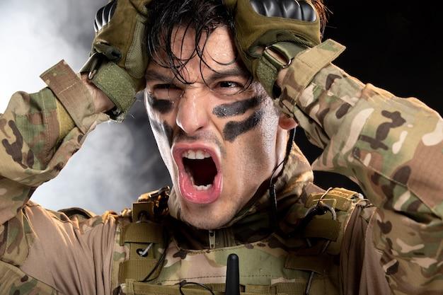 Portret van jonge soldaat in camouflage op donkere muur