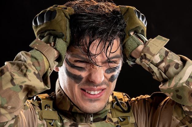 Portret van jonge soldaat in camouflage op zwarte muur