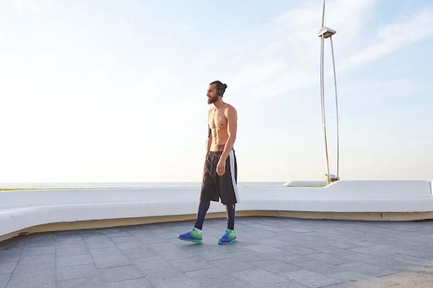 Portret van jonge sportieve man met baard, rust na het joggen, wandelingen aan zee, favoriete liedje luisteren op koptelefoon. geniet van een geweldige ochtend!