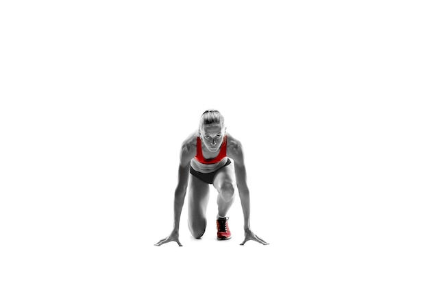 Portret van jonge sportieve vrouw bij startblok van race geïsoleerd over witte studio achtergrond. de sprinter, jogger, oefening, training, fitness, training, jogging concept.