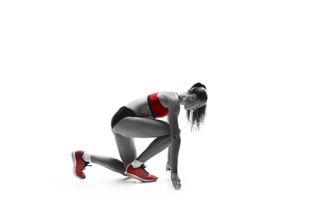 Portret van jonge sportieve vrouw bij startblok van race geïsoleerd over witte studio background