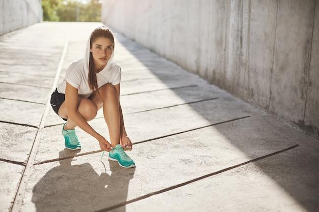 Portret van jonge sportieve vrouw die haar sneakers rijgt om haar dagelijkse joggingsessie te nemen.
