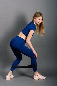Portret van jonge sportieve vrouw lachend zittend en training geïsoleerd op grijs