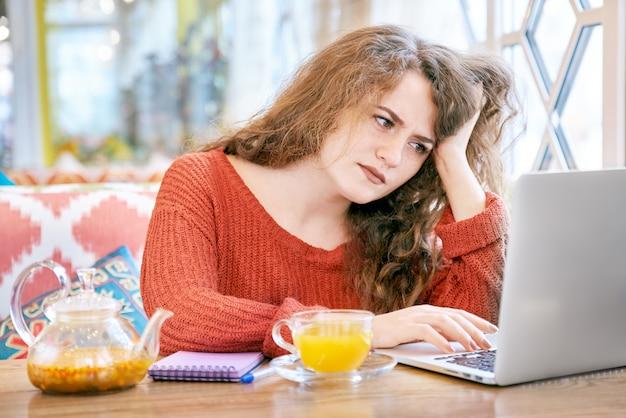 Portret van jonge sproeterige witte studente met lang krullend rood haar die met laptop met een gefrustreerde, vermoeide uitdrukking werken.