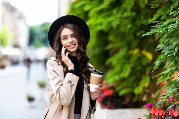 Portret van jonge stedelijke vrouw lopend en pratend op mobiele telefoon op straat
