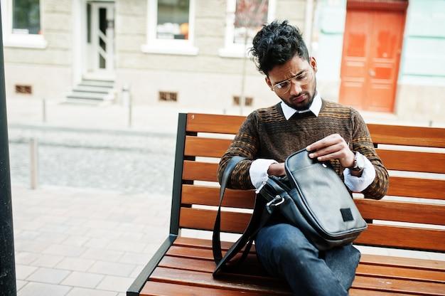 Portret van jonge stijlvolle indiase man model pose in straat, zittend op een bankje met handtas.