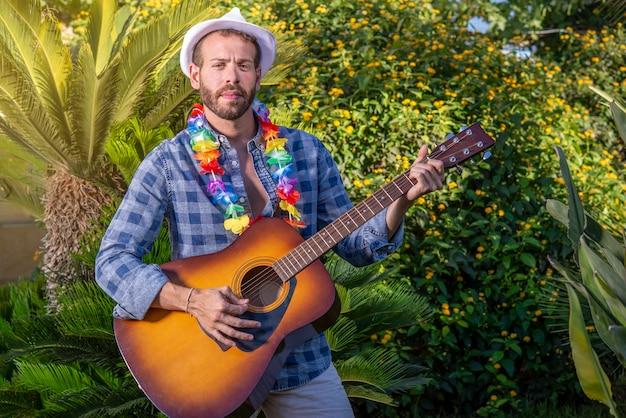 Portret van jonge stijlvolle man met gitaar in de hand