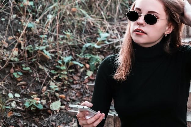 Portret van jonge stijlvolle moderne vrouw in zonnebril en zwarte coltrui zittend op de trappen in het park met mobiele telefoon in haar hand. vrouw geniet van frisse lucht, rust uit de drukte van de stad