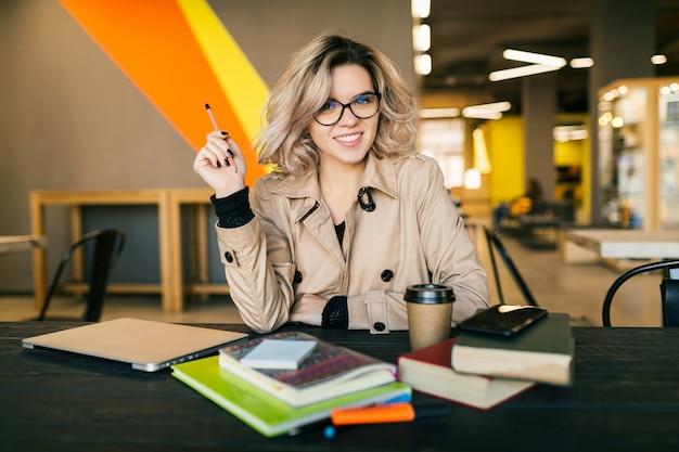 Portret van jonge stijlvolle vrouw met een idee, zittend aan tafel in trenchcoat bezig met laptop in co-working office, bril, glimlachend, gelukkig, positief, druk